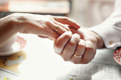 Bride and groom holding hands. In a cafe Stock Photo