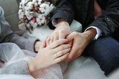 Bride and groom holding hands in the car Stock Images