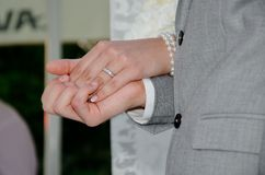 Bride and groom holding hands. Close up of bride and groom holding hands at wedding ceremony Royalty Free Stock Images