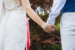 Bride and groom holding hands, close-up. Royalty Free Stock Image