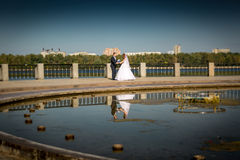 Bride and groom holding hands and dancing at riverbank Royalty Free Stock Photo