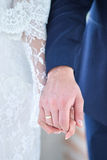 Bride and Groom Holding Hands. Detail of groom holding his bride's hand in his royalty free stock photos