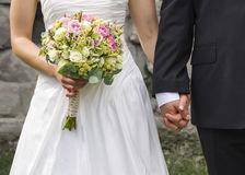 Bride and groom holding hands. Detail of newlyweds, bride and groom,  holding hands and flower bouquet, front view Royalty Free Stock Photo