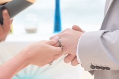 Bride and Groom Holding hands and exchanging rings stock image