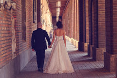 Bride and groom holding hands. In hallway Royalty Free Stock Image