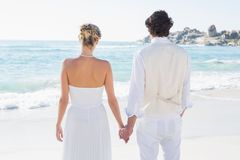 Bride and groom holding hands looking out to sea Stock Photography