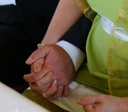 Bride and groom holding hands during marriage ceremony in civil registry office stock images