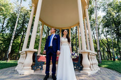 Bride and groom holding hands near the arbour in the park. Wedding couple in love at wedding day Royalty Free Stock Image