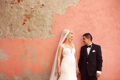 Bride and groom holding hands near old wall Stock Images