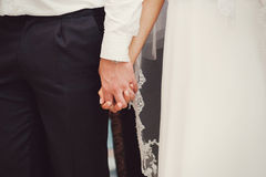 Bride and groom holding hands outdoors Royalty Free Stock Photos