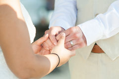Bride and groom holding hands outdoors Stock Images
