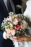 Bride and Groom Holding Hands. Bride and groom pictured holding hands over a bouquet of beautiful flowers Stock Photography