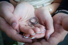 Bride and groom holding hands with the ring on the wedding photo session Stock Image