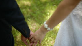 Bride and groom holding hands in summer day