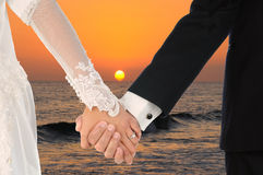 Bride and Groom Holding Hands at Sunset Stock Photography