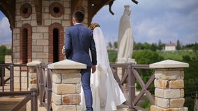 Bride and groom are holding hands walking along an ancient castle with stone statues stock video