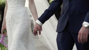 Bride and groom holding hands and walking in a city. Slow motion stock video footage
