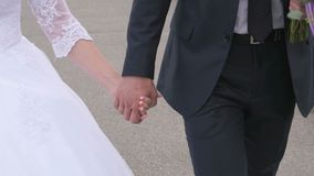 Bride and groom holding hands during walking stock footage