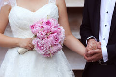 Bride and groom holding hands and wedding bouquet. Hands of bride and groom with beautiful bouquet Stock Photography