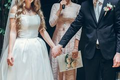 Bride and groom holding hands at wedding ceremony indoors. cerem. Ony master performing speech Royalty Free Stock Images