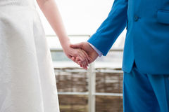 Bride and groom holding hands. Bride and groom with wedding dress and suit, holding hands, mid section, side view. outdoor Royalty Free Stock Images