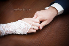 Bride and groom holding hands on wood background Stock Image