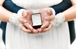 Bride and groom holding open box with wedding rings Royalty Free Stock Photos