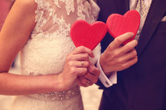 Bride and groom holding red hearts Stock Photos