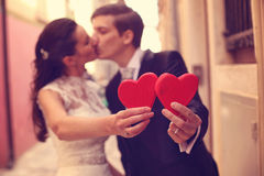 Bride and groom holding red hearts Royalty Free Stock Photos