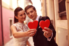 Bride and groom holding red hearts Stock Photo