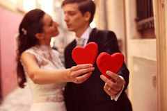 Bride and groom holding red hearts. Beautiful Bride and groom holding red hearts Stock Image