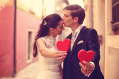 Bride and groom holding red hearts Stock Image