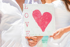Bride and groom holding sign with love word on tropical sea back Royalty Free Stock Image