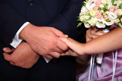 Bride and groom holding their hands. At their wedding Stock Photos