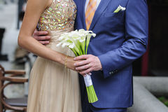Bride and groom holding a wedding bouquet of callas Royalty Free Stock Photo