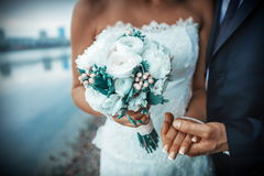 Bride and groom holding wedding bouquet. Hand Royalty Free Stock Images
