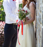 Bride and groom holding wedding bouquet Stock Image