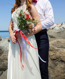 Bride and groom holding wedding bouquet Stock Photos