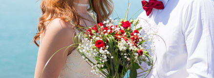 Bride and groom holding wedding bouquet Stock Images