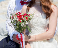 Bride and groom holding wedding bouquet Stock Photo