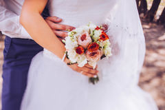 Bride and groom holding wedding bouquet together, outdoor. Stock Images