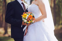 Bride and groom holding wedding bouquet together, outdoor. Love. Royalty Free Stock Photography
