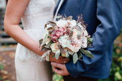 Bride and groom holding wedding bouquet together, outdoor Stock Photo