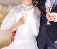 Bride and groom holding wedding champagne glasses Stock Images