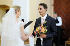 Bride and groom holding wedding rings Royalty Free Stock Photos