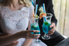 Bride and groom holding wineglass with blue cocktail Royalty Free Stock Photo