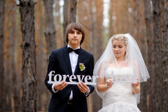 Bride and groom holding wooden letters love forever Royalty Free Stock Photos