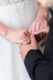 Bride and groom holds hands. The bride and groom in wedding dresses standing next to each other and holding hands. On the finger of the bride wearing a wedding Royalty Free Stock Images