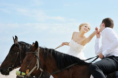 Bride and groom on a horses by the sea Royalty Free Stock Image