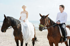 Bride and groom on a horses by the sea Stock Photo